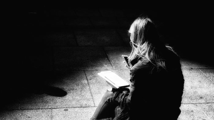 A woman, looking alone and isolated, with her back to the camera, staring down at her phone in the shadows.
