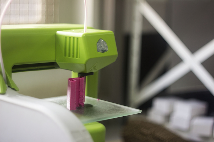 Close-up of a brightly colored, simple-looking 3d printer, fabricating a small, unknown object.