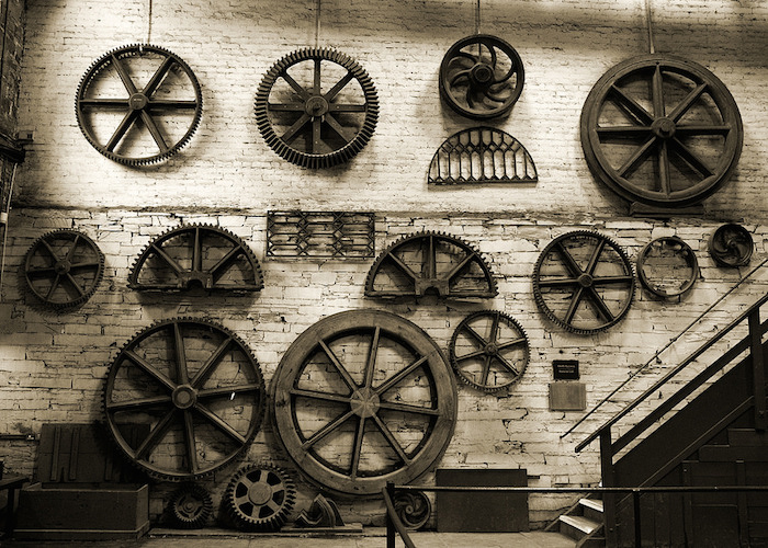 Wall of wheels, cogs and other machine parts displayed on a wall, as in a museum display.