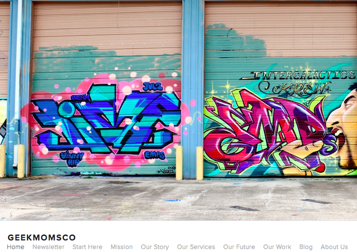 "Screenshot of the Geek Moms & Co homepage: features a large splash photo of colorful street art across a series of garage doors; it says ""Intergalactic Krew"" and shows a man shoving letters into his mouth. The menu items include Mission, Our Story, Our Services, Our Work and About Us."