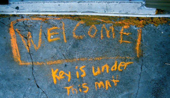 Chalk text on a concrete stoop reading Welcome: Key is Under This Mat.