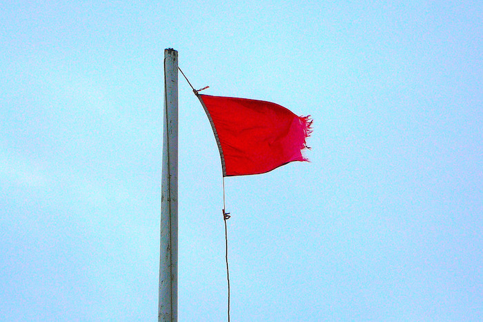 Tattered red flag flying in the wind.