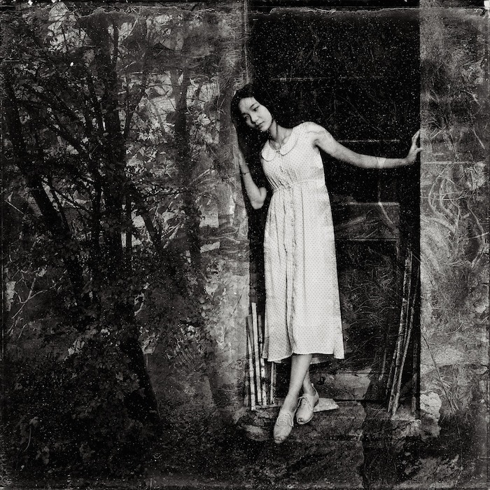 Black and white image of a woman in a plain dress leaning in a doorway; on the surrounding walls is the vague impression of dark woods, trees and mosses.