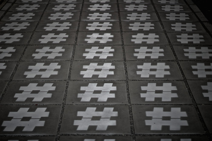Series of hashtags printed on square concrete slabs.