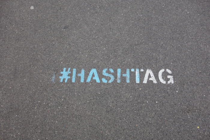 "The word ""hashtag"" with a pound sign stenciled and spray-painted on a street."