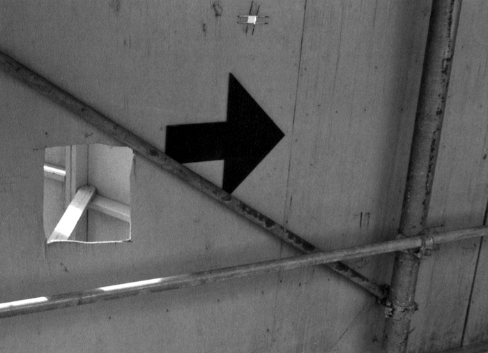 Black arrow drawn on the wood of a construction site.