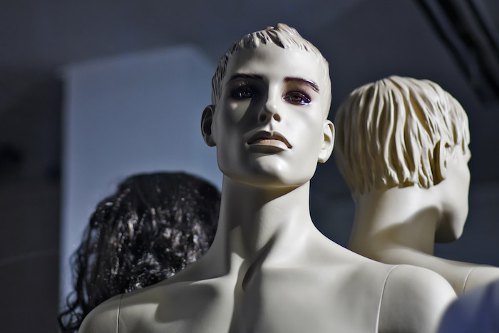 From the photographer: White skinned male mannequin, lighted from the right side of the image, sitting behind a large shop window. It has strong features, colorful eyes and plastic hair. Behind it there are two other models, another white one and a female mannequin with shiny black hair.