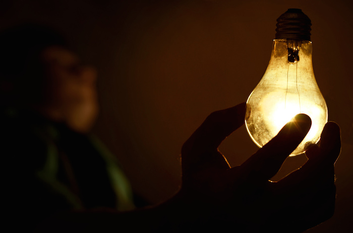 A person reaching for a lightbulb illuminated in a dark room.