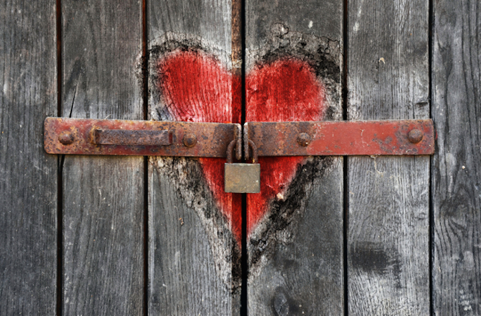 A heart drawn over a locked wooden door; a bar and lock intersect the heart.
