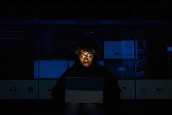 A woman of color alone in a dark room, laptop screen illuminating her face.