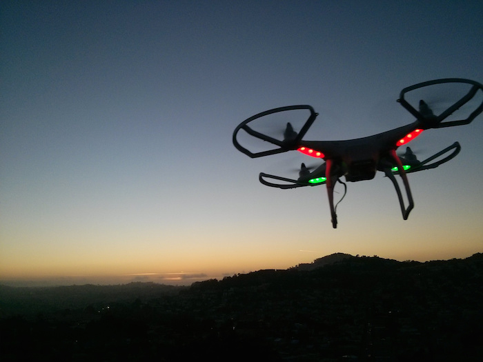 A small drone with four sets of propellers flying against a sunset.
