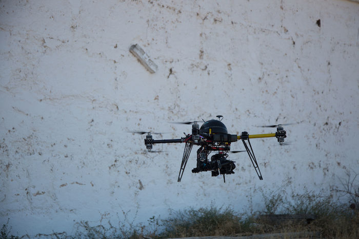 A small, robotic-looking drone equipped with a video camera is pictured against some grass and a concrete wall.