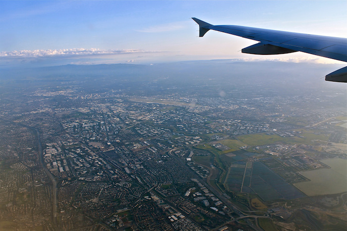 Ariel view of Silicon Valley: grids of housing and greenery bisected by roads, the tip of the airplane wing just visible in the right-hand corner.