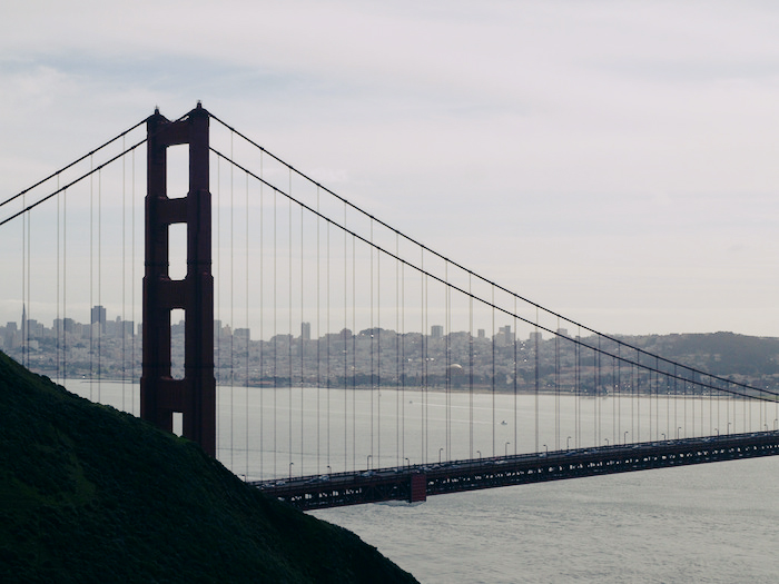 A view of the Golden Gate Bridge from a bluff facing the city; San Francisco's high-rises are visible between the bridge beams on a slightly foggy day.