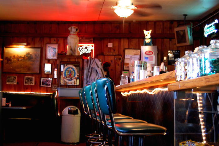 A row of empty bar stools at a dive bar, Christmas lights strewn along the bar top and posters on the wall in the background.