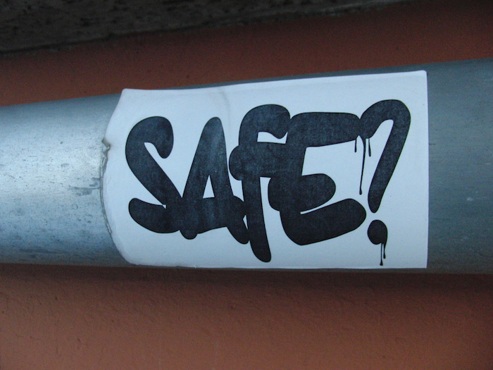 "A sticker on a metal pipe that reads ""Safe?"" in bold letters."
