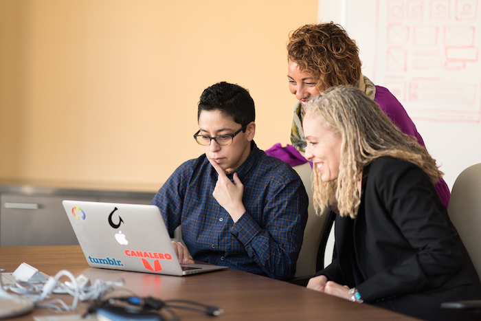 Collaborators of color gather around a laptop in a conference room.