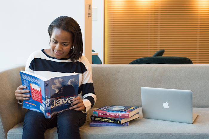 "A black woman reading a book on Java programming, next to a stack of other technical books including ""Compiler Design."""