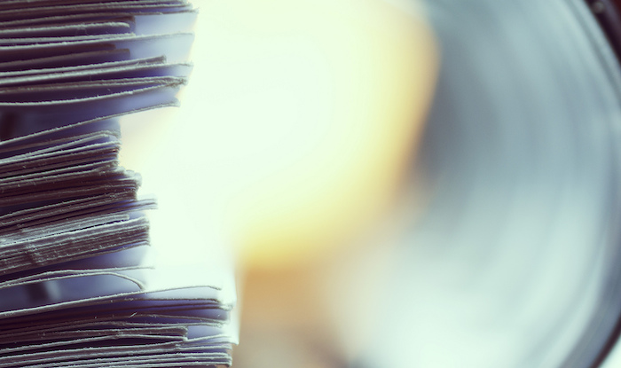 Close-up on the edge of a stack of papers in a binder.
