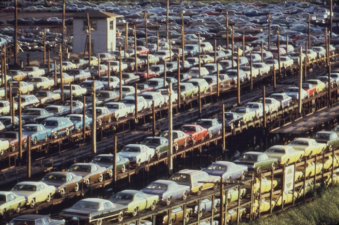 Rows of hundreds of cars lined up in Detroit for transport on a railway.