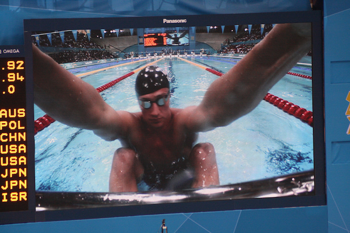 Ryan Lochte preparing to thrust off of the pool wall in competition.