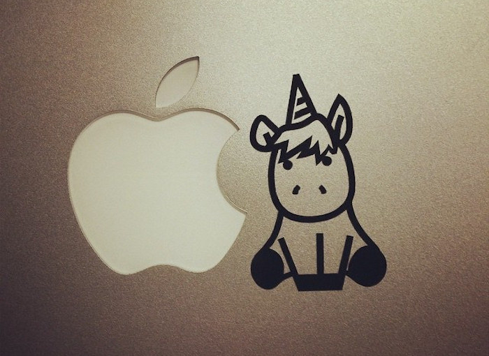 A unicorn drawn on the lid of a laptop next to the Apple logo.