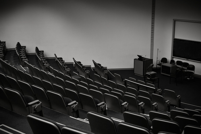 Rows and rows of empty seats in an auditorium-style lecture room.