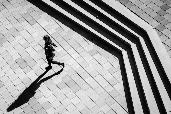 A lone student walking across a brick walkway, outlined dramatically by rows of stairs in black and white.