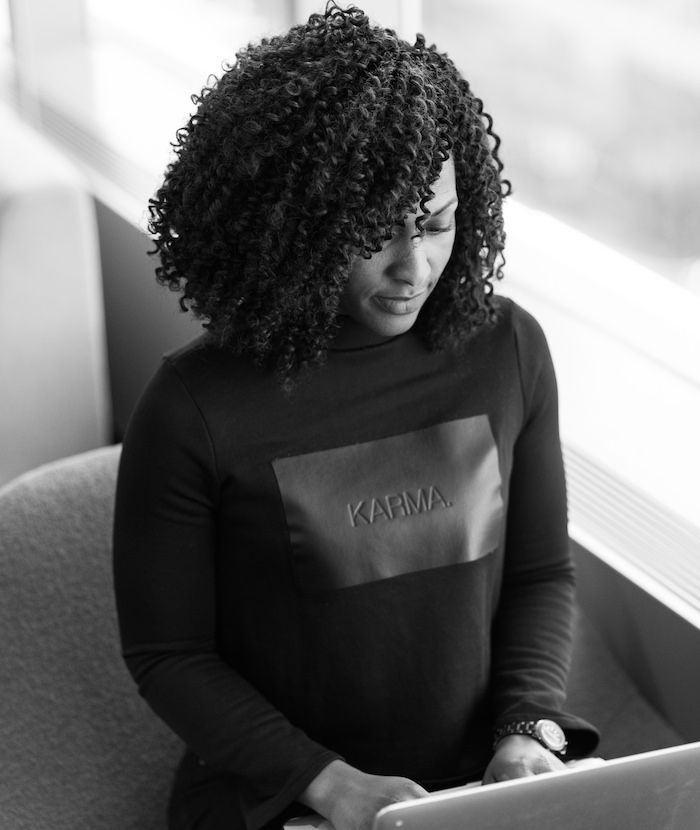 "Photo of a black woman typing on a laptop. She is wearing a sweatshirt that says ""Karma""."