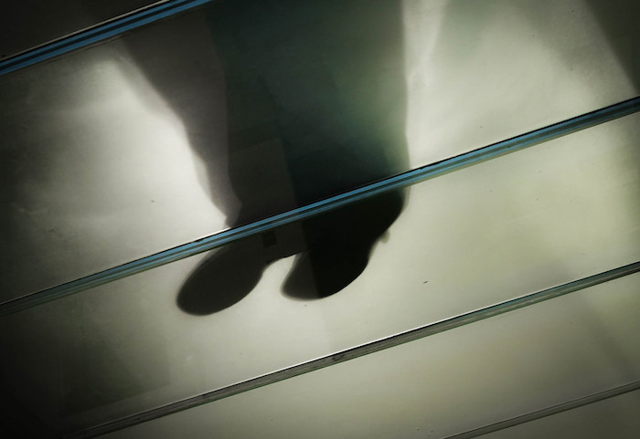 "Photographic implementation of the ""glass ceiling"": someone standing on a glass floor, viewed from below."