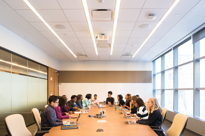 A large tech conference room with a number of women of color technologists in a meeting.