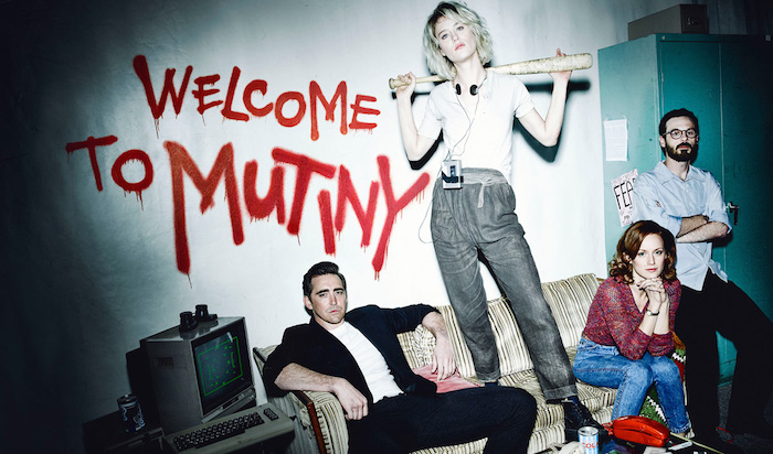 "The main characters in Halt and Catch Fire situated around a couch, with the words ""Welcome to Mutiny"" spray-painted on the wall behind them. Character Cameron is standing on the couch, holding a baseball bat behind her head."