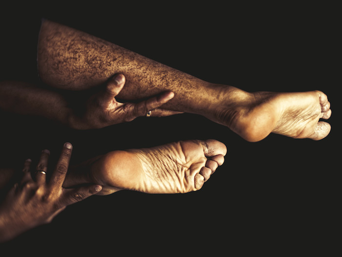 Close-up of two black people holding their ankles and lower calves in their hands, feet upturned.