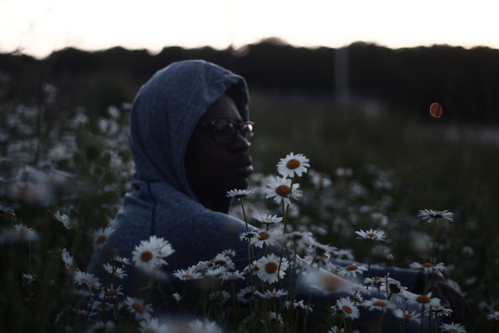 A black man in a hoodie and glasses sits in a field of daisies.
