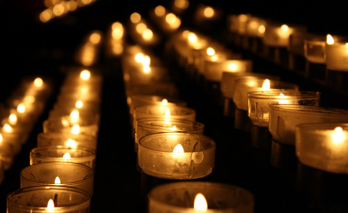 Rows of lit small candles glowing in the dark.