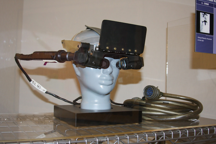 The first VR prototype: a bulky contraption with a mounted screen over the eyes, thick wires and cords attached to a mannequin head.