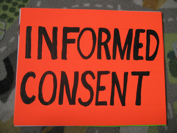 A large red sign reading 'Informed Consent', written in blocky permanent marker.