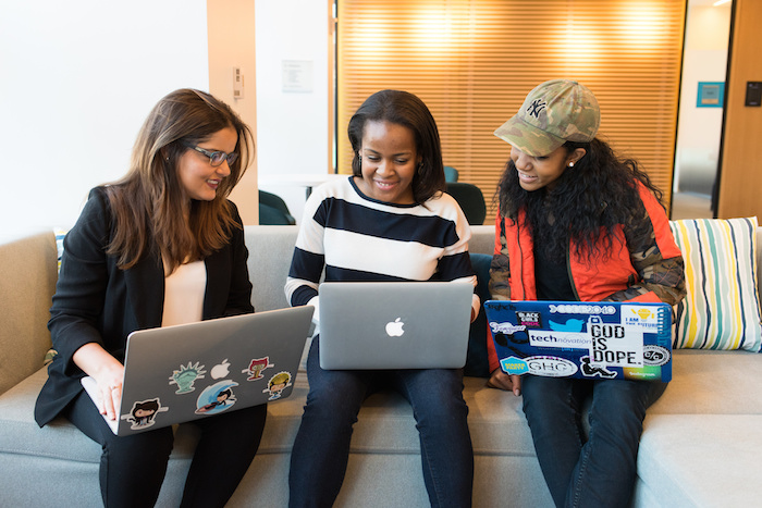 Three women of color collaborating on a couch, each with laptops adorned with stickers.