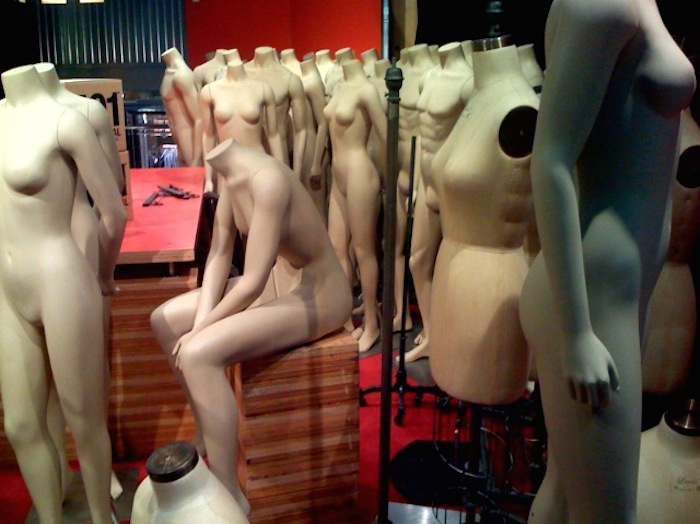 Series of undressed, headless white mannequins lined up in an empty store.
