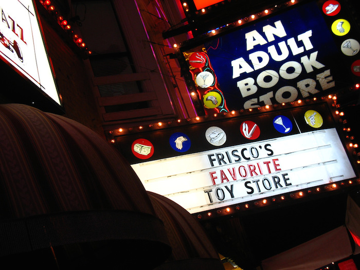 Movie-style billboard for a brightly-lit adult book store reading 'Frisco's favorite toy store.'