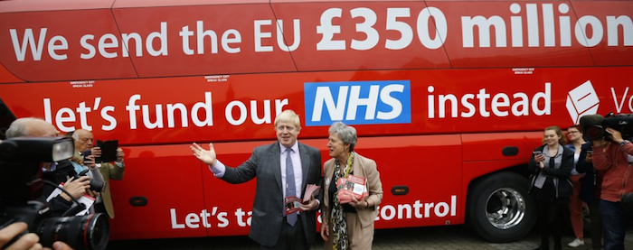 "Image of bus emblazoned with ""We send the EU £350 million. Let's fund our NHS instead."" Campaigners speak to the media outside of the bus."