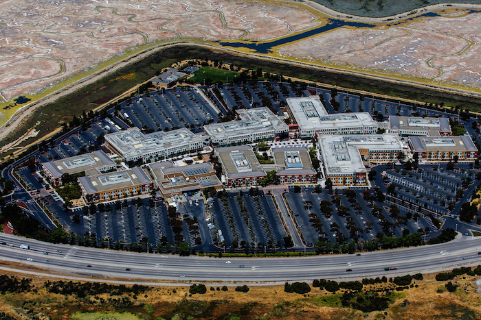 Aerial image of the Facebook campus: shaped in a triangle, featuring large compounds and huge parking lots.