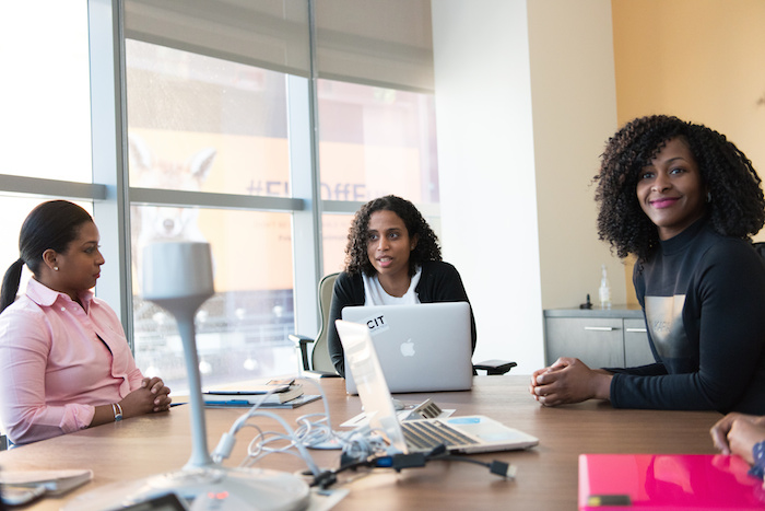 Three black women in tech gathered around a conference room with their laptops.
