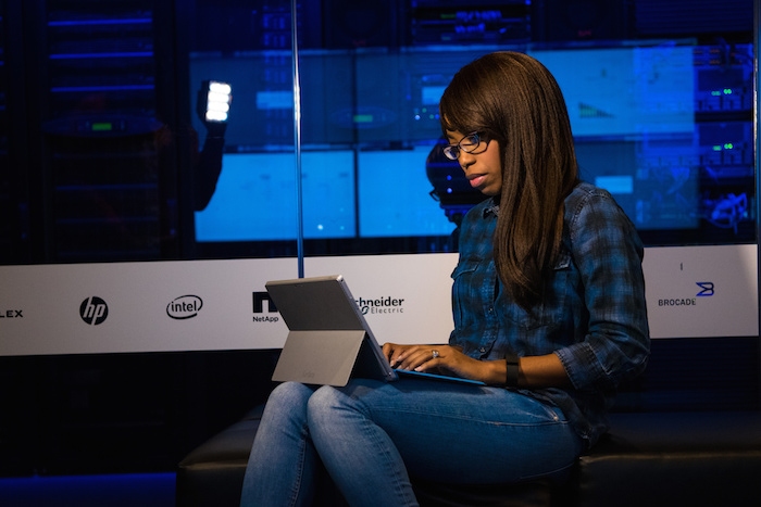 A black woman working on a laptop in a data center.
