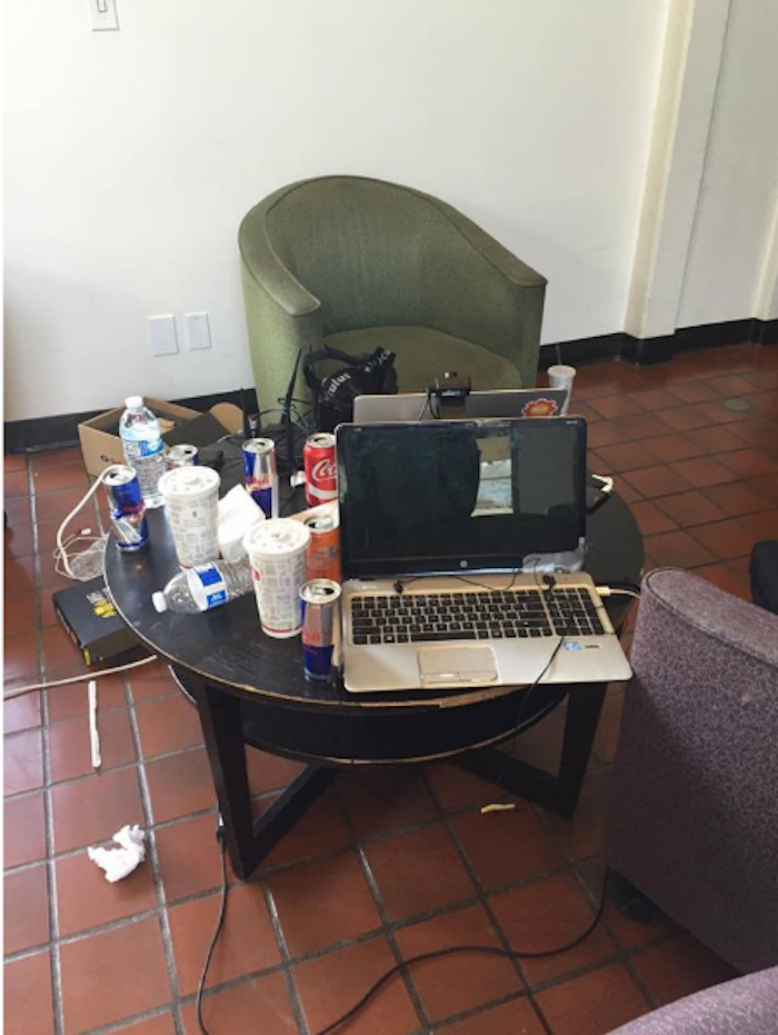 An empty green velvet chair by a small table covered in a laptop, cords and dozens of soft and energy drinks.