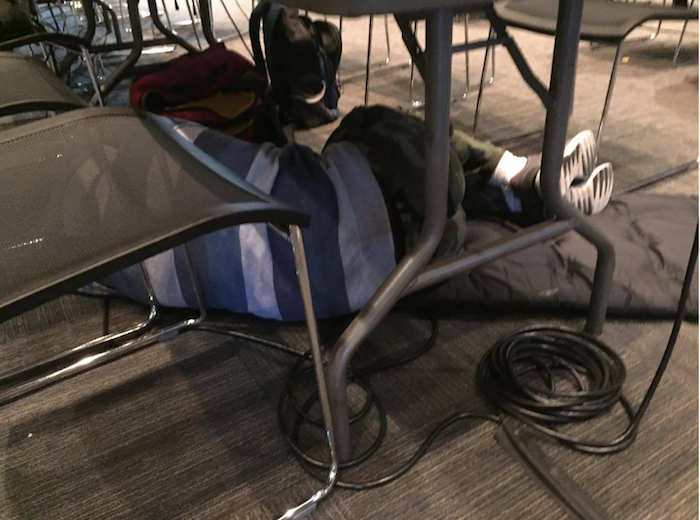 A person (face non-visible) sleeping under a folding chair at a hackaton.