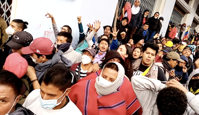 Protestors fill the streets of Quito, wearing masks and arms upraised.
