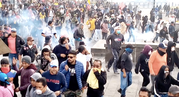 Protestors in Quito scatter from tear gas thrown at the crowd.