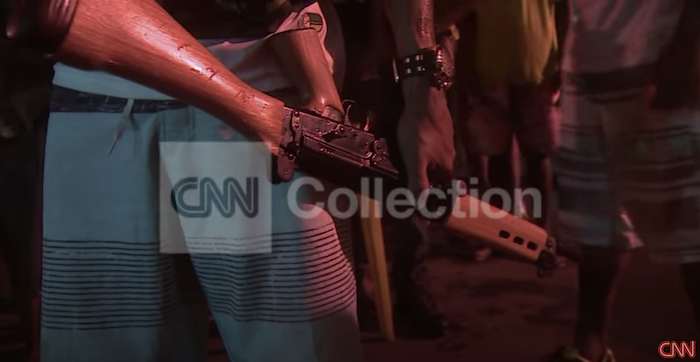 A black youth holds a large rifle in this CNN screenshot.