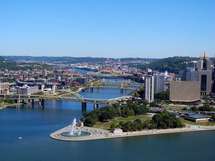 Photo of downtown Pittsburgh, the City of Steel. The land reaches a point where two rivers converge; large steel traffic bridges cross into the distance.
